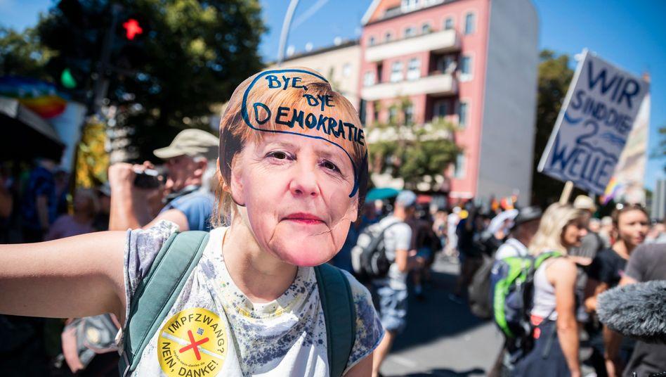 Frau mit Merkel-Maske auf der Berliner Demo: Wo fängt die gemeinsame Wirklichkeit an?