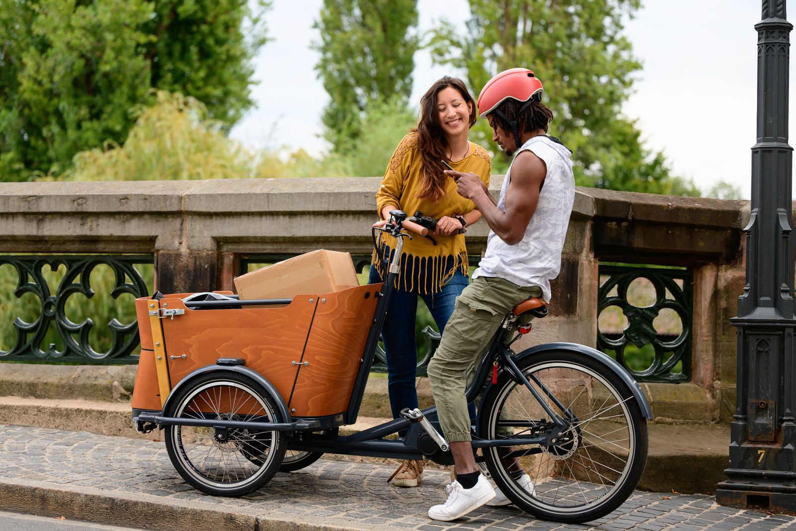Couple with bicycle and cargo bike in urban surrounding