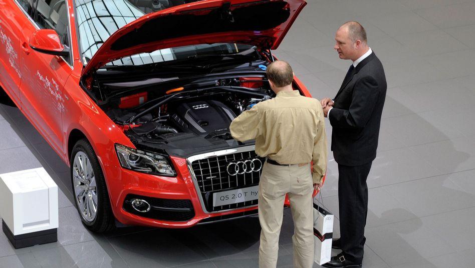 Blick unter die Haube: Zwei Männer schauen in den Motorraum eines Audi Q5