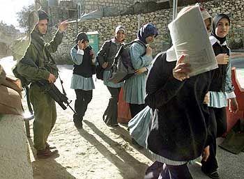 Kein Tag ohne Waffen: Palästinensische Schüler passieren einen israelischen Checkpoint in Hebron