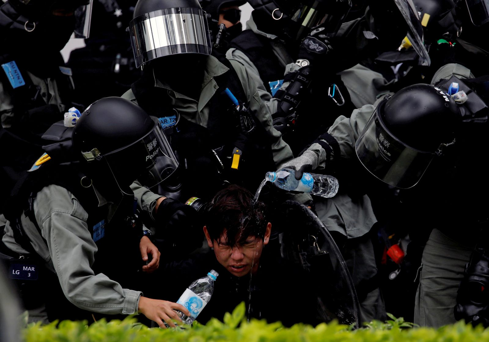 Riot police pour water on the face of anti-government protester who was pepper sprayed while getting detained after an anti-parallel trading protest at Sheung Shui, a border town in Hong Kong