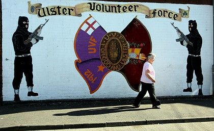 A woman passes a mural for the Ulster Voluteer Force, an outlawed Protestant group, in east Belfast.