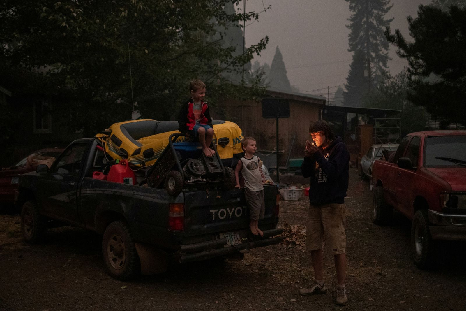 Father and twin sons prepare to evacuate their home from the Obenchain Fire in Butte Falls, Oregon
