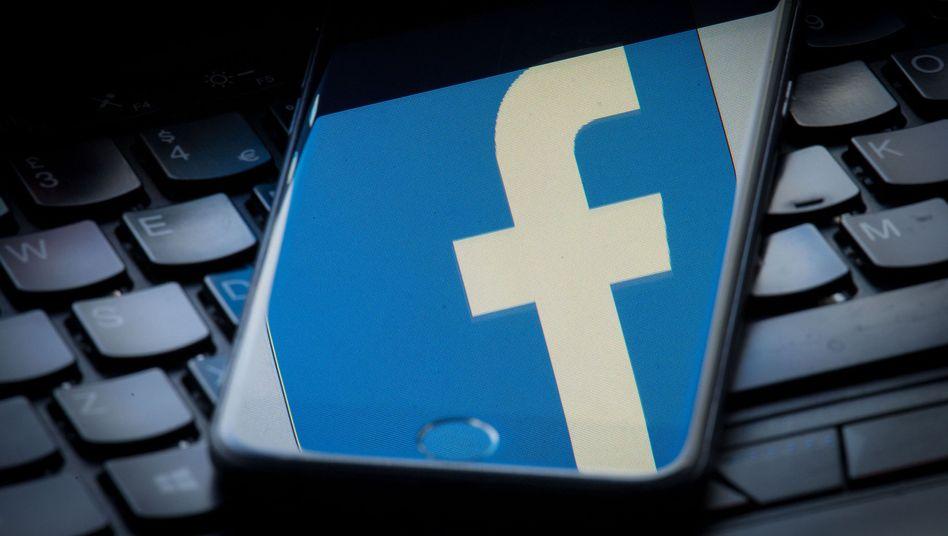 Das Facebook-Logo spiegelt sich auf einem Smartphone