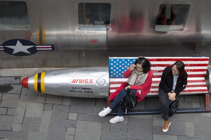 Zwei Frauen in China auf einer Bank mit US-Flagge