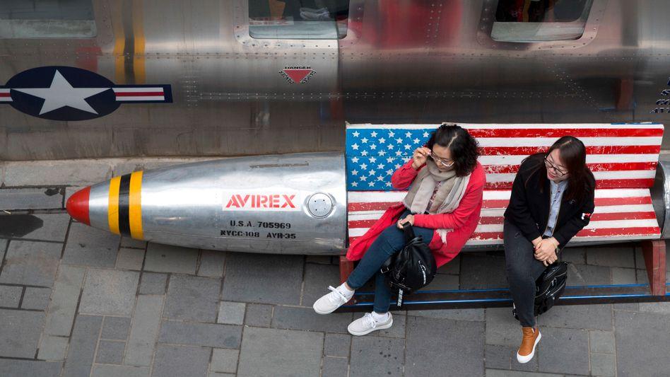 Zwei Frauen sitzen in Peking auf einer Bank, die mit der US Flagge dekoriert ist