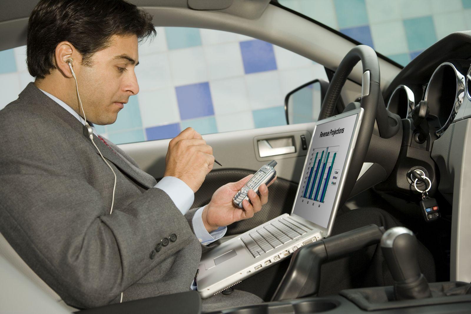 NICHT MEHR VERWENDEN! - Geschäftsmann im Auto mit Handy, Notebook und Headset