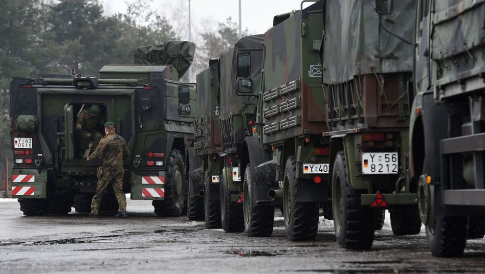 "German military vehicles lined up ready for transport to Lithuania as part of NATO's ""Enhanced Forward Presence."""