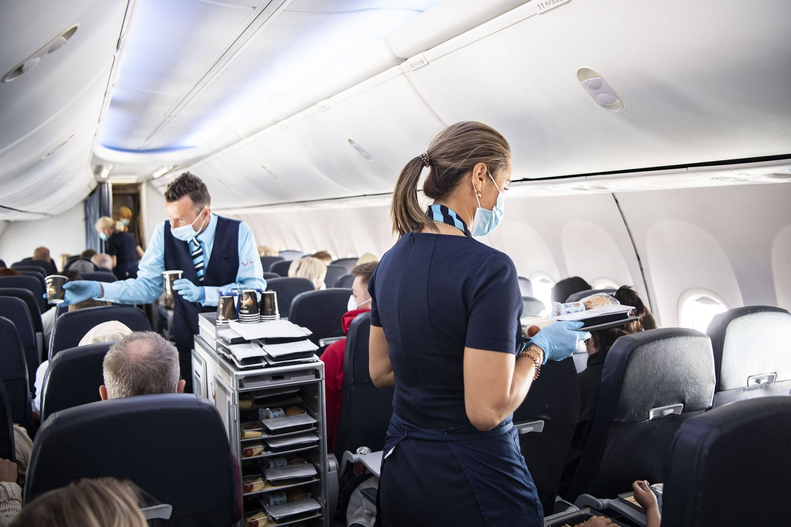 Flight attendants wearing face masks and plastic gloves during the first chartered TUI flight from Stockholm, Sweden on