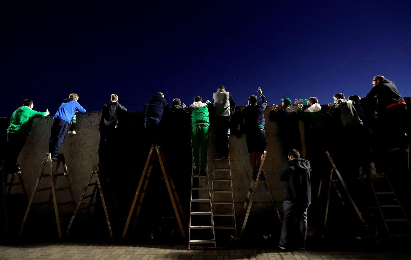 Fans watch a soccer match from behind a wall in Prague