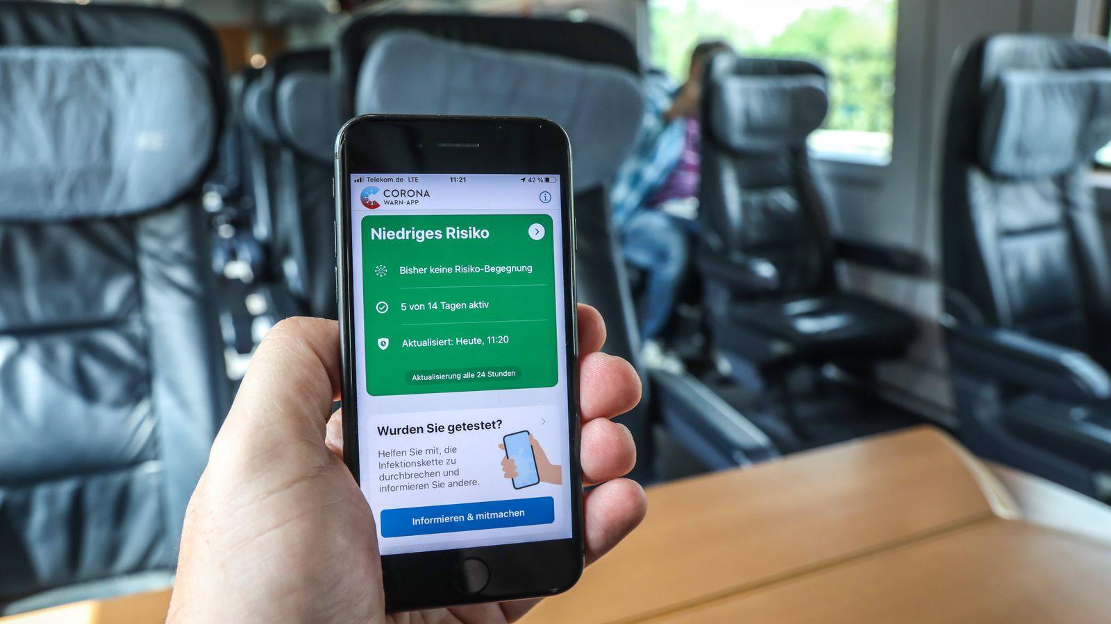 Unterwegs mit einem Intercity-Express-Zug (ICE) der Deutschen Bahn - dabei Nutzung der Corona-Warn-App auf einem Smartp
