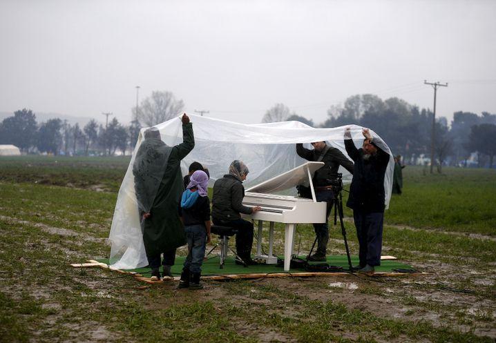 Ai Weiwei (rechts) hält im März 2016 in Idomeni eine Plane über eine syrische Klavierspielerin