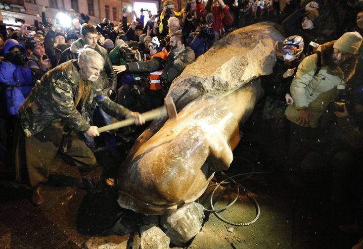 Im Blitzlichtgewitter: Demonstrant hämmert auf die gestürzte Lenin-Statue ein
