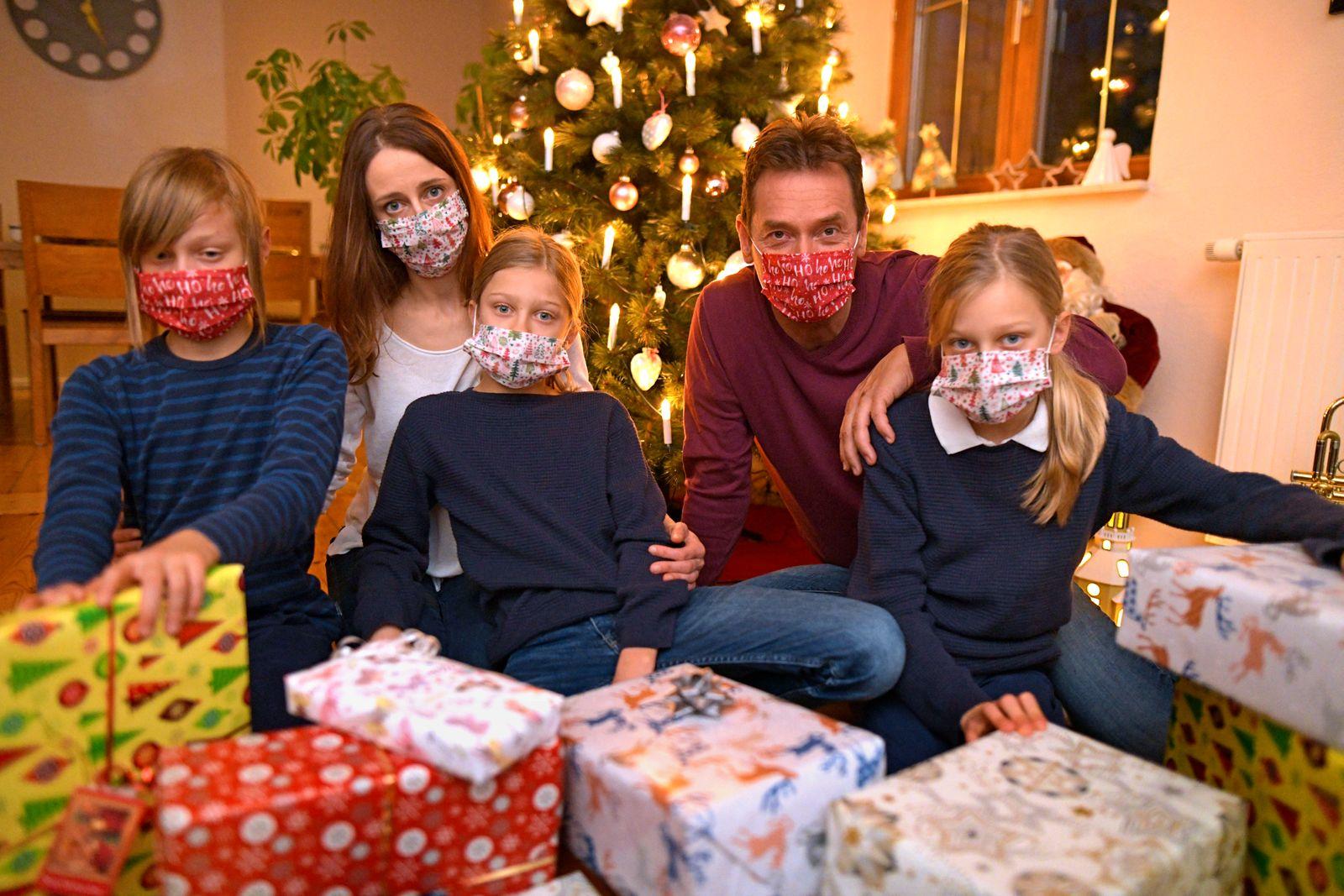 24.11.2020, (Modelreleased). Symbolbild, Eine Familie im Allgäu sitzt mit Mund-Nasenschutz-Masken am Heiligen Abend vor