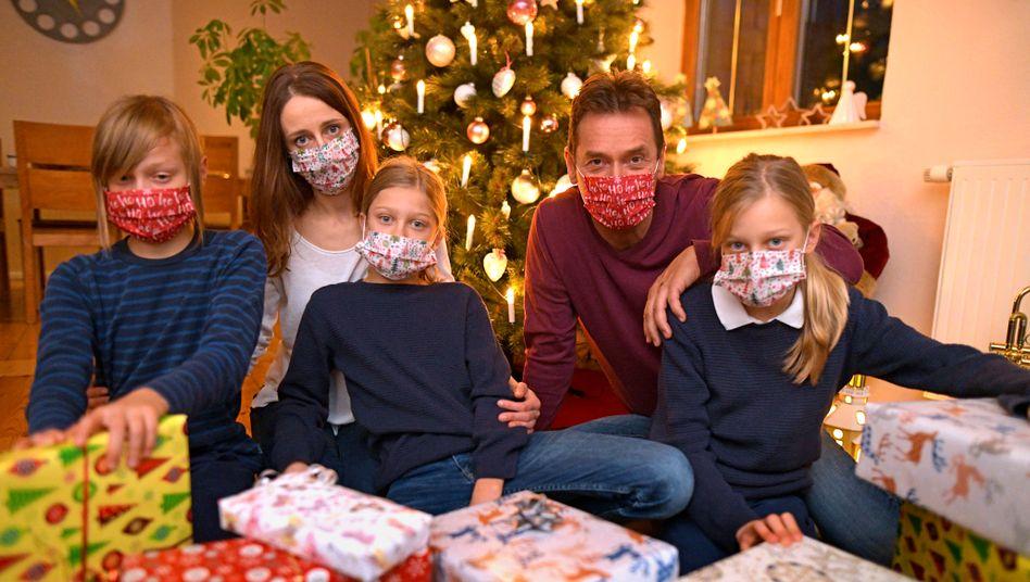 Eine Weihnachtsbescherung, bei der die gesamte Kernfamilie Masken trägt, gibt es höchstwahrscheinlich nur auf diesem gestellten Symbolbild
