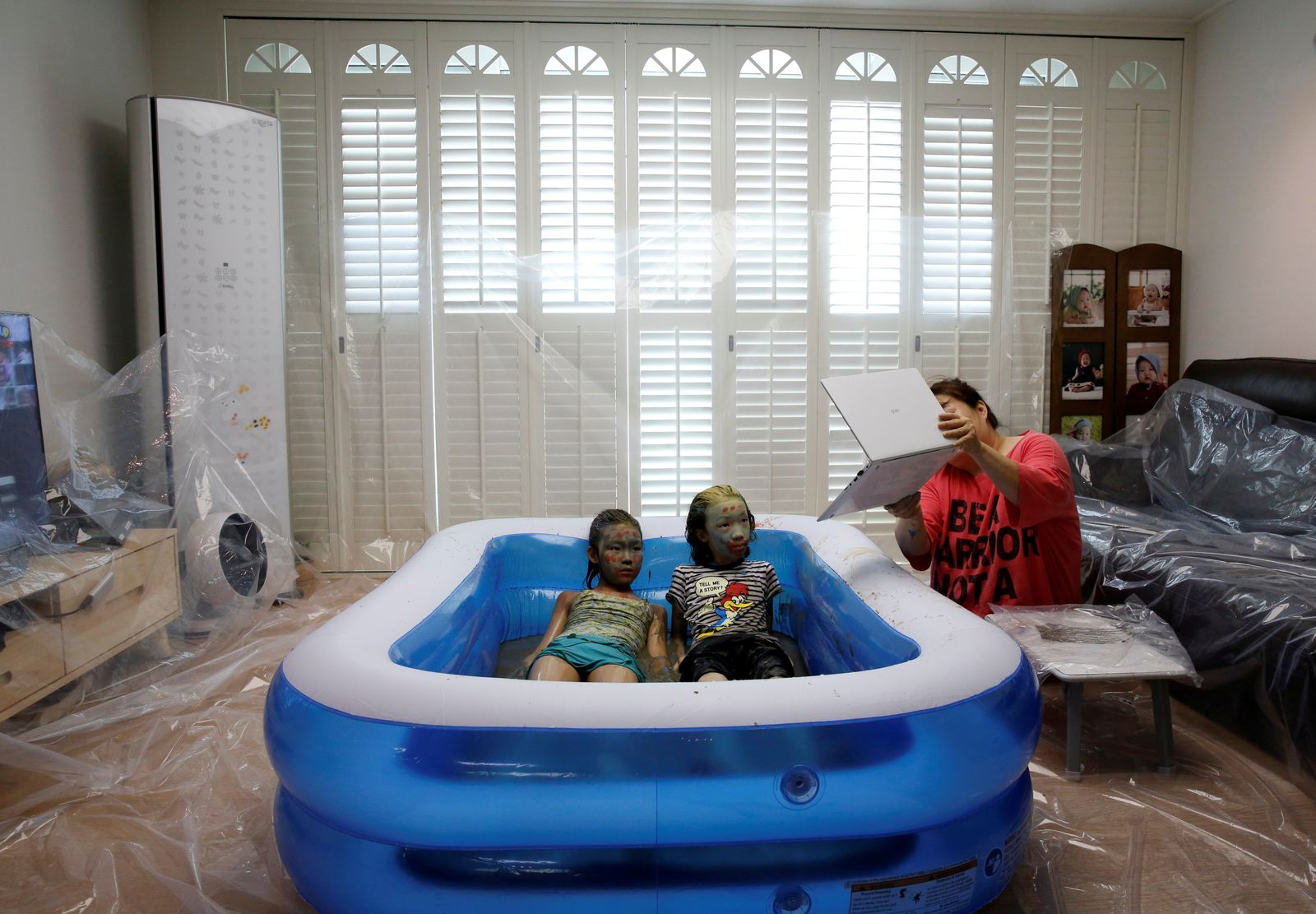 Children play in a mud pool during the Online Boryeong Mud Festival at their home during a live streaming event, in Gwangju