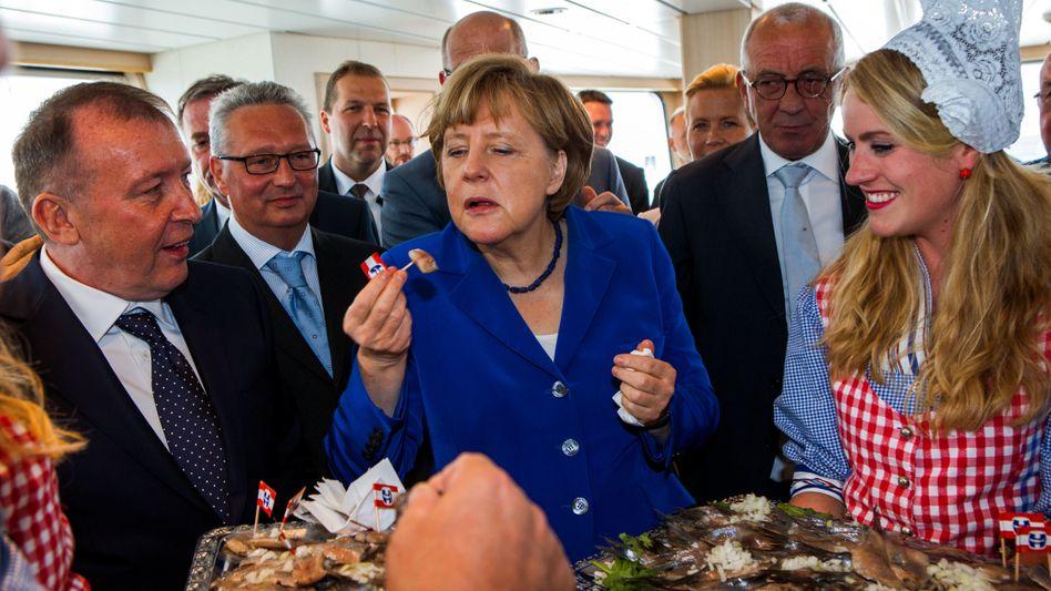 """Gute Verbindungen: Angela Merkel 2015 mit dem Fischereiunternehmer Diederik Parlevliet (l.) nach der Taufe des Trawlers """"Mark"""""""