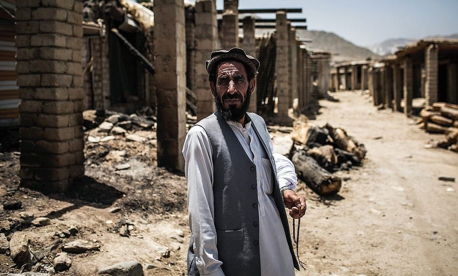 Commander Kamagul in front of the ruins of a village bazaar in Achin District.