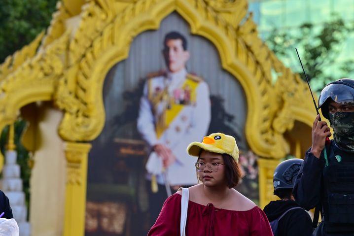 Studentin Panusaya vor einem Porträt von Rama X. in Bangkok