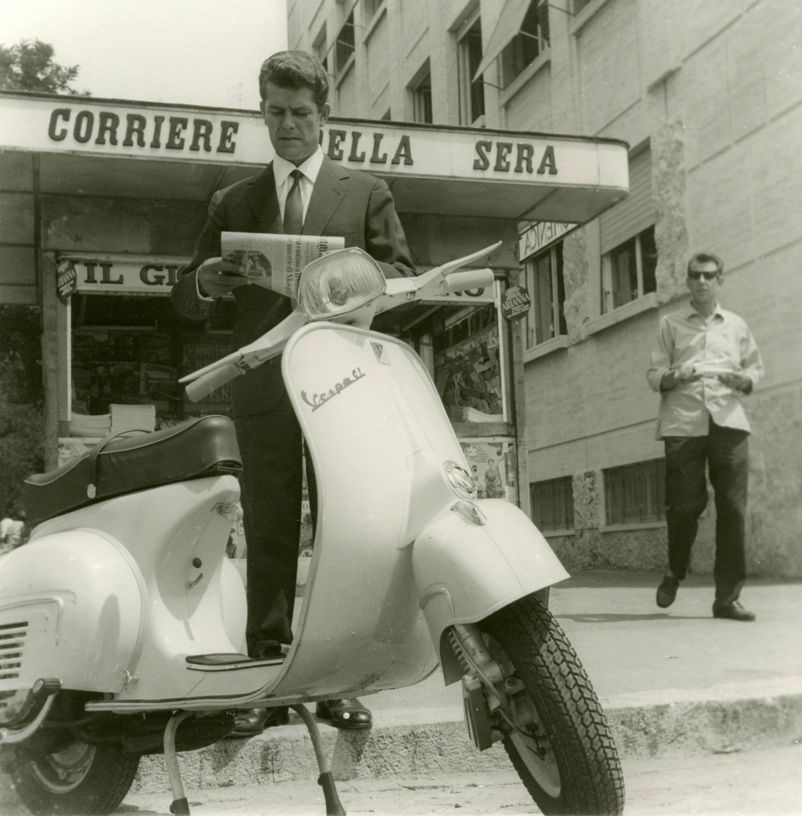 Advertising Piaggio Vespa A man buys a newspaper and approaching a Vespa Rome Italy x09304x