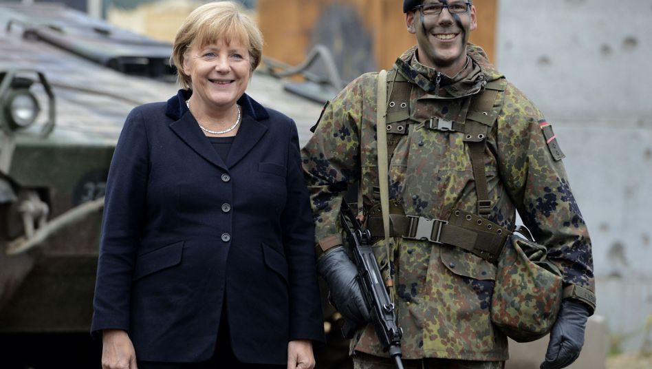 Angela Merkel poses with a soldier in Munster: Germany's military restraint is also a product of the chancellor herself.
