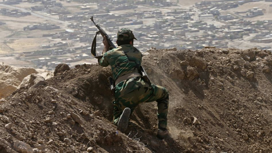 A Kurdish Peshmerga fighter moving into position in a battle with Islamic State.