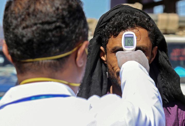 In der südjemenitischen Stadt Taizz wird einem Mann im Zuge der Coronakrise die Temperatur gemessen