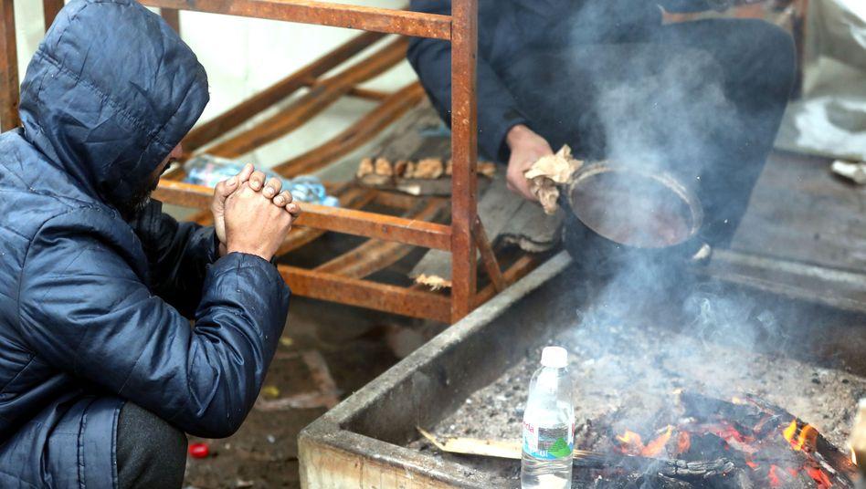 Menschen versuchen im zerstörten Flüchtlingslager Lipa, sich an einem offenen Feuer zu wärmen (Foto vom 1. Januar)