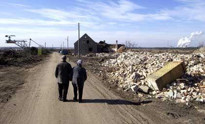Entvölkerung im Osten: Ein altes Ehepaar läuft über die Dorfstraße von Horno in Brandenburg.