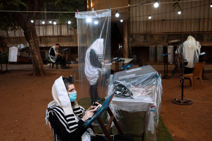 Ultraorthodoxe Juden tragen während eines Morgengebetes Gesichtsmasken