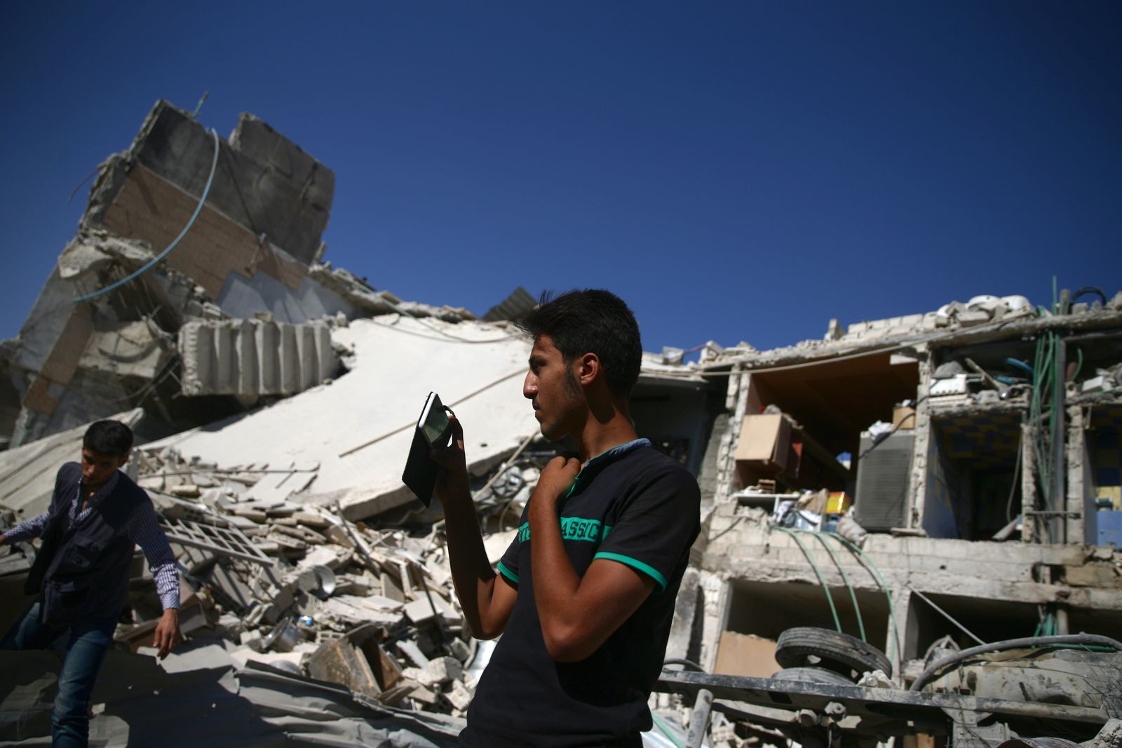 A man takes pictures with his mobile phone at a site by an airstrike in the rebel held Douma neighborhood of Damascus
