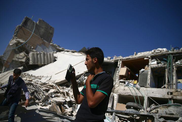 Augenzeuge mit Handy: Ein junger Syrer dokumentiert nach einem Luftangriff die Schäden