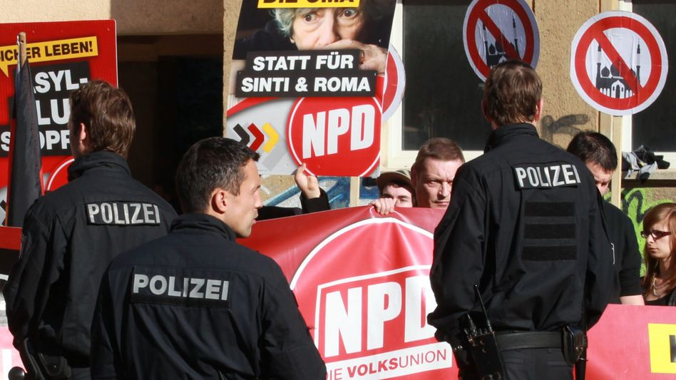 A poster of the kind that a German town took offense to, held up here at an NPD rally in Gera on Saturday.