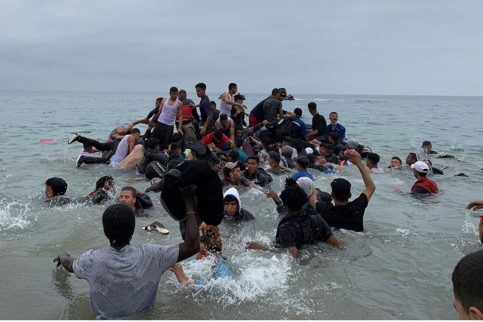 Migrants manage to grab a boat of the Moroccan authorities near the coast of Fnideq (Morocco) in an attempt to cross ove