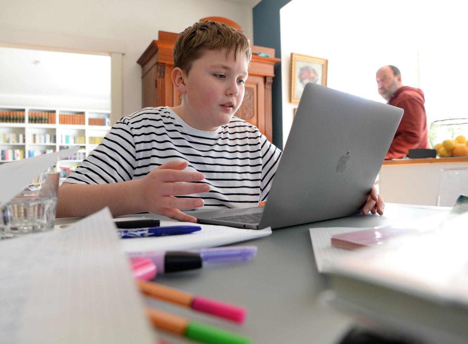 Ein Junge (model released) l?st Schulaufgeben an seinem Laptop MR=Yes