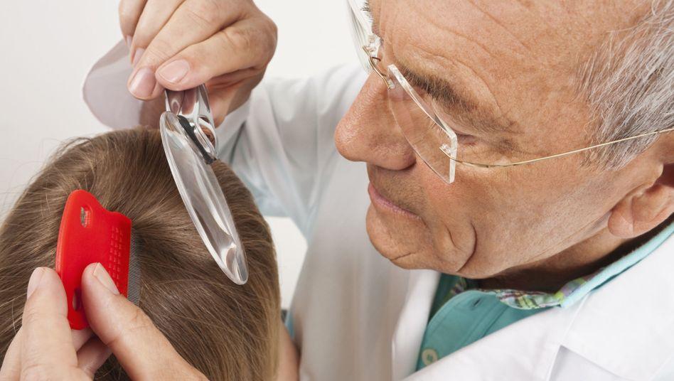 Arzt mit Lupe: Läusekämme sind ein bewährtes Mittel gegen Kopfläuse