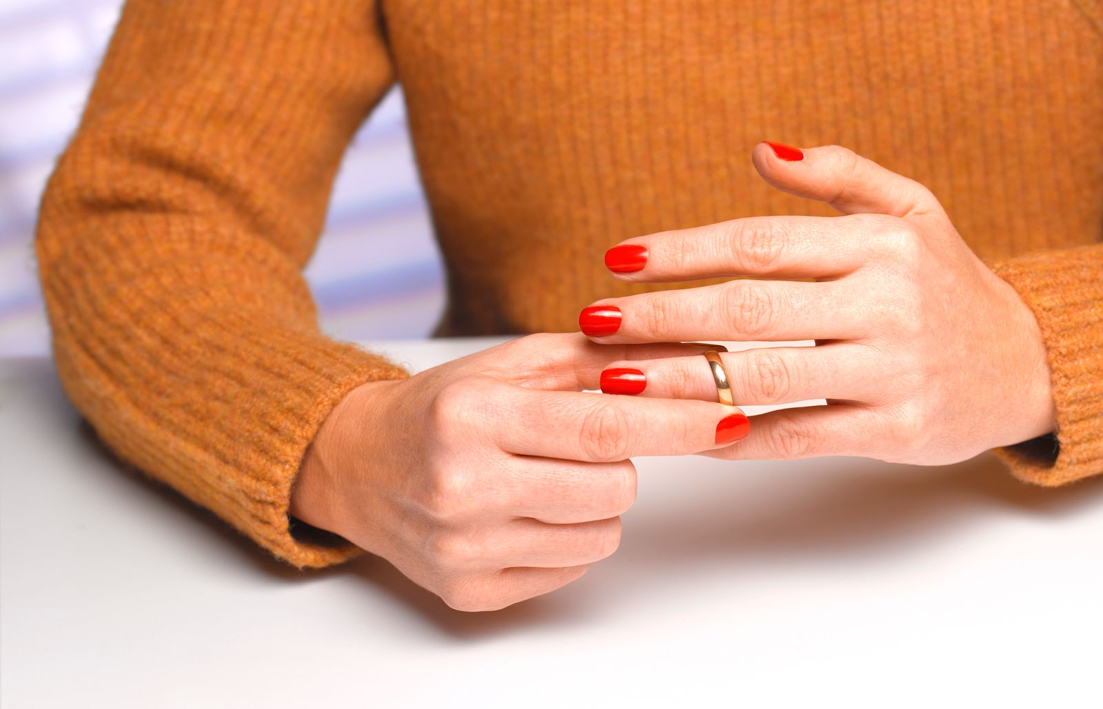 Divorced woman taking off wedding ring