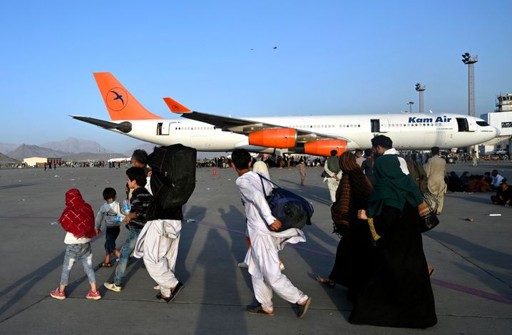 Afghan families walk by aircraft at the Kabul airport.