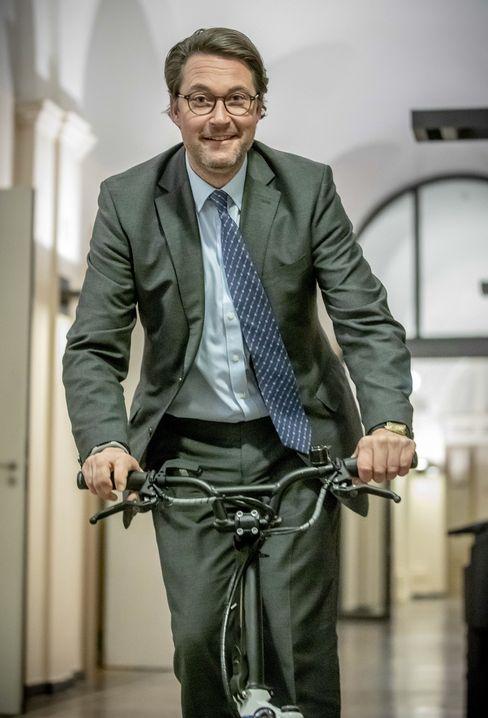 Andreas Scheuer fährt mit einem E-Roller durch die Gänge des Verkehrsministeriums