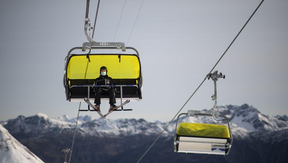 Skifahrer mit Mund-Nasen-Schutz in der Seilbahn