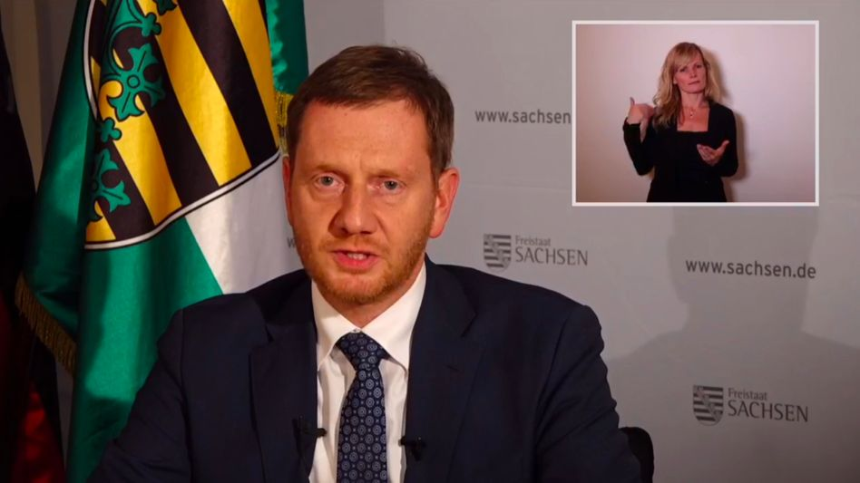 Dolmetscherin Carla Vogel zeigt, was Ministerpräsident Michael Kretschmer sagt