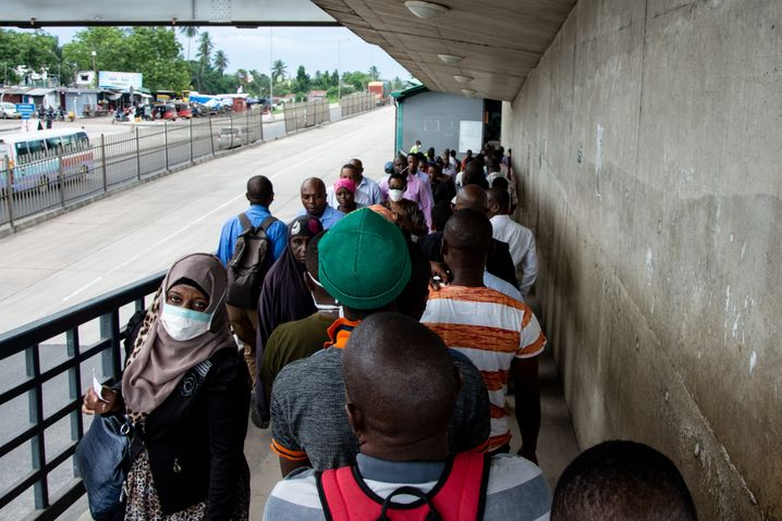 Menschen auf einer Fußgängerbrücke in Dar es Salaam