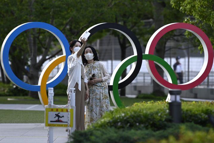 Touristinnen machen ein Foto von sich vor den Olympischen Ringen in Tokio (Symbolbild)