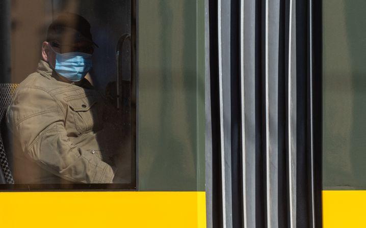 Mann mit Mund-Nasen-Schutz in der Straßenbahn