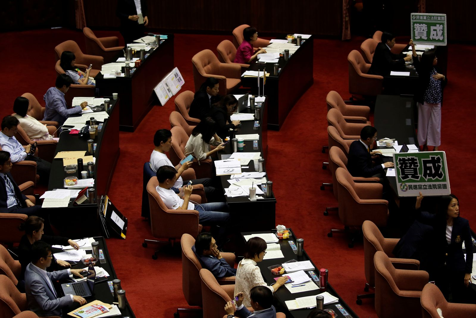 """Member of Taiwan's ruling Democratic Progressive Party hold a sign with Chinese word """"Agree"""" during a parliament vote on three draft bills of a same-sex marriage law, inside the Legislative Yuan in Taipei"""