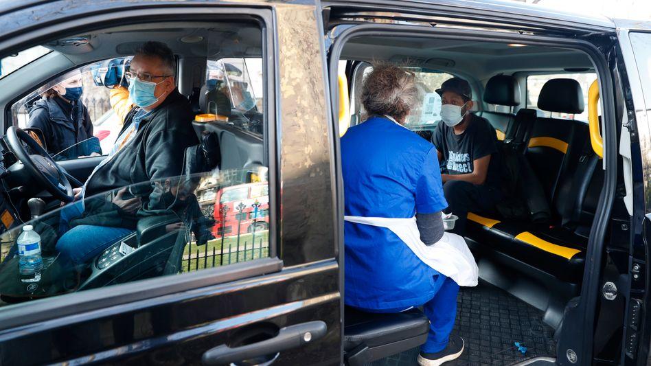 Eine Ärztin bereitet die nächste Impfung auf dem Rücksitz eines »Vaxi Taxi« vor