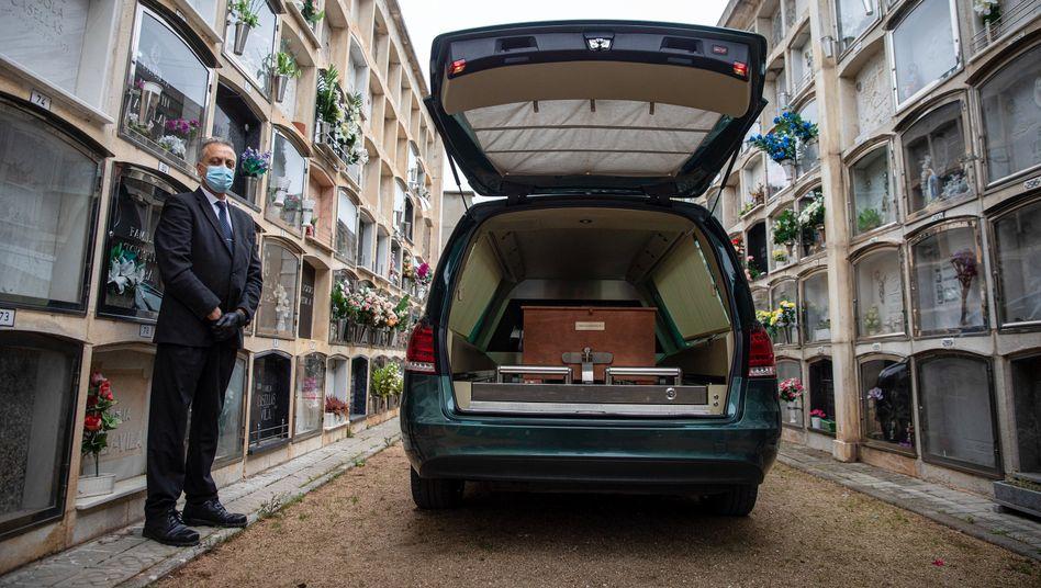 Ein Mitarbeiter eines Bestattungsunternehmens wartet im spanischen Girona neben einem Leichenwagen