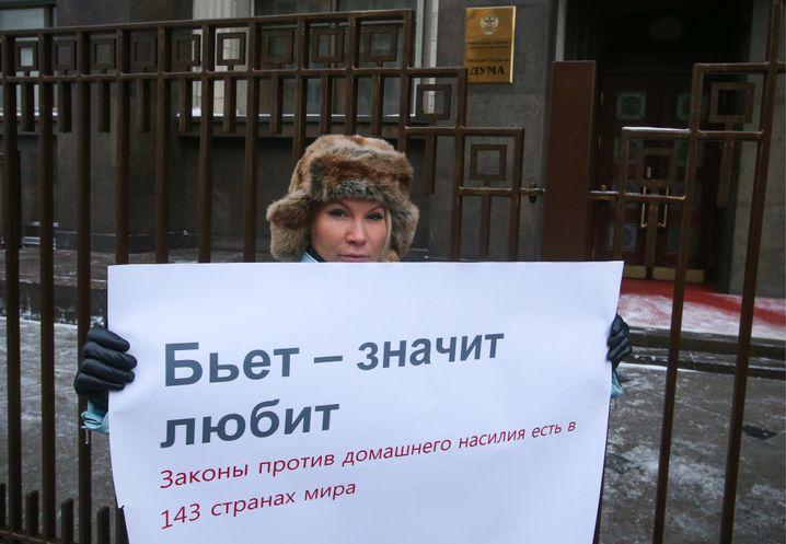 """Frauenrechtlerin Aljona Popowa vor der Duma 2017: """"Wenn er schlägt, liebt er - Gesetze gegen häusliche Gewalt gibt es in 143 Ländern"""", steht auf dem Plakat"""