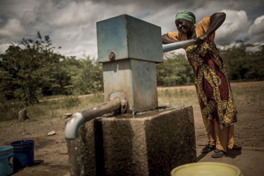 An einer von sechs Pumpen, die im Laufe des Programms angelegt wurden, holt Aisha Bahari Wasser für ihre Familie