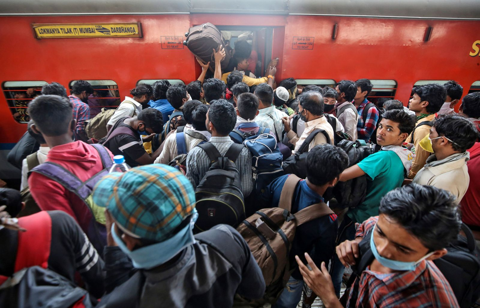 Migrant workers and their families board an overcrowded passenger train, after government imposed restrictions on public gatherings in attempts to prevent spread of coronavirus disease, in Mumbai
